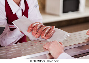 Midsection of butcher displaying sausages in front of...