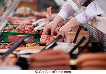Butcher's Hands Arranging Meat In Display Cabinet - Closeup...