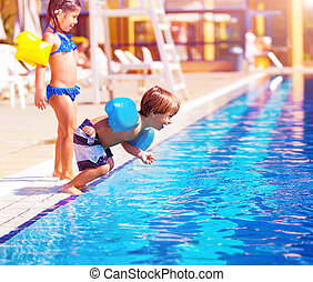 Little boy jumping into the pool - Cute little boy jumping...