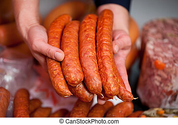 Butcher's Hands Displaying Handful Of Sausages - Butcher's...
