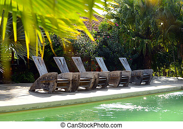 pool chairs on deck at a hotel in tropics
