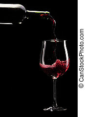 Red wine being poured into a glass infront of black...