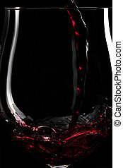 Close-up of red wine splashing into a glass infront of black...