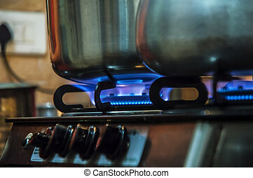 Two Pots on fire on kitchen gas stove which is having the...