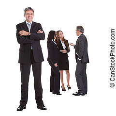 Businessman Standing In Front Of His Colleagues Over White...