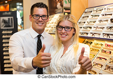 Customer in optometrists shop choosing the eyeglasses -...