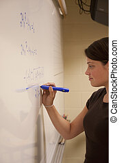 Female student solving an Algebra equation on a whiteboard.
