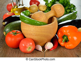 Wooden mortar and fresh vegetables on a brown table