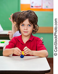 Boy Holding Clay Model At Desk - Cute little boy holding...