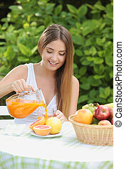 healthy living - Young woman relaxes in the garden drinking...