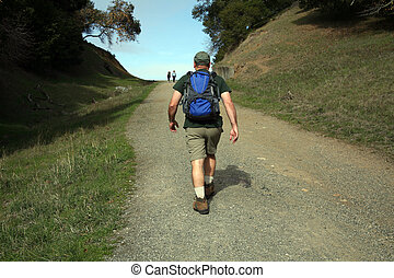 hit the trail - Man striding uphill on a trail with backpack...