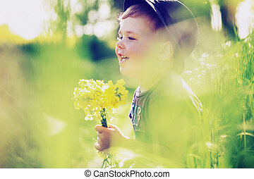 Cheerful child playing on the meadow