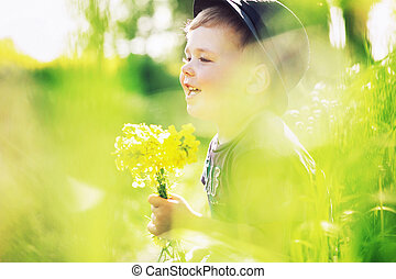 Smiling boy holding yellow flowers - Smiling kid holding...