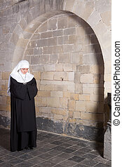 Young nun in old church - Young novice standing near the old...