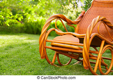 Empty rocking chair over grass at summer sunset
