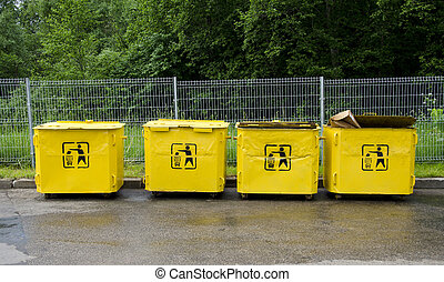 four old yellow trashcans in parking place