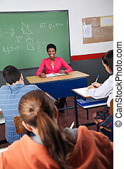 Female Teacher Sitting With Students In Classroom - Portrait...