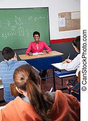 hembra, profesor, Sentado, con, estudiantes, en, aula