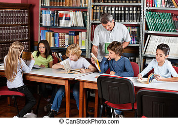 Teacher Showing Book To Schoolboy In Library - Happy mature...