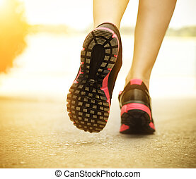 Runner feet running on road closeup on shoes Woman fitness...