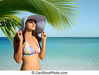 Girl with Panama under a palm tree on the beach.