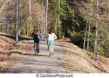 Two girls riding a bike in the park