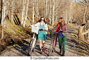Two girls walking with bikes in the park on a path in a...