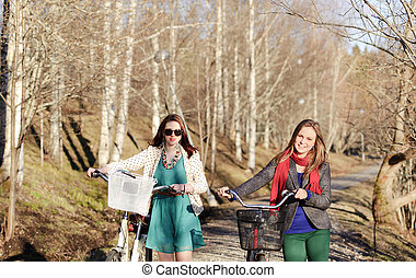 Two girls walking with bikes in the park