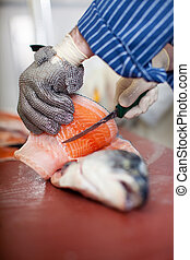 Worker's Hands Cutting Fish With Knife At Table - Closeup of...