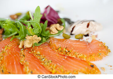 salmon slices with arugula on white plate
