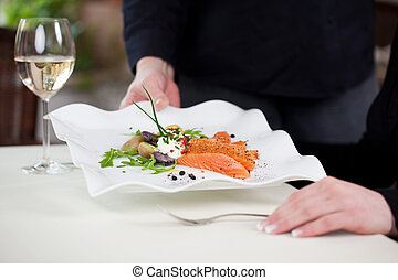 waitress serving tasty fish dish to female guest