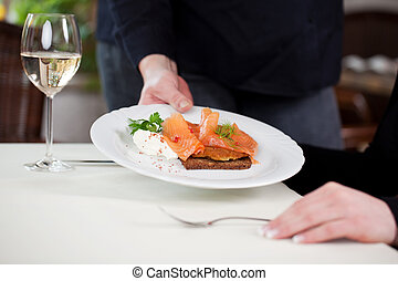 waitress serving salmon on bread dish at table