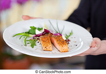 Waitress Displaying Salmon Dish In Restaurant - Cropped...