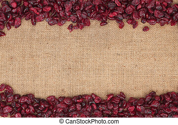 Cranberries are lying on sackcloth with space for text