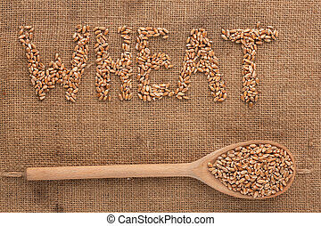 Inscription wheat with a wooden spoon on burlap