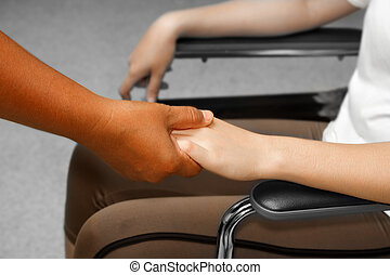 Doctor holding  patient 's hand in a wheelchair