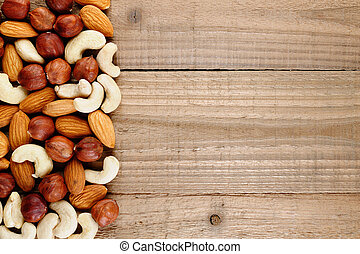 Mix of hazelnuts, almonds and cashew nuts on wooden...