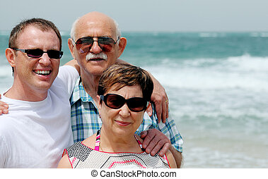 adult son with his parents  walking on the beach
