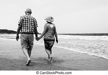 backview of senior couple walking on sandy beach