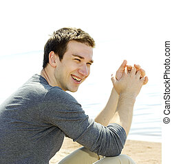 Portrait of a handsome young man sitting on the beach