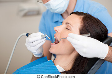 Examining Female Mouth In Clinic - Mature dentist examining...