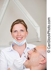 Female Dentist Examining Male Patients Mouth In Clinic