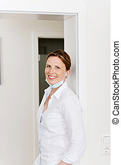 Female Dentist Leaning On Doorway In Clinic