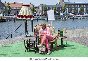 woman reading outside near the water