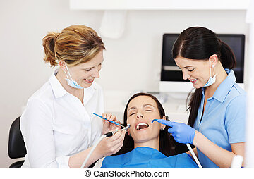 Dentists Examining Patients Mouth With Tools In Clinic -...
