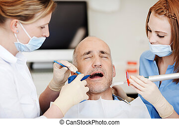 Dentists Using Dental Tools - Female dentists using dental...