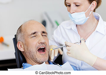 Dentist Injecting Anesthesia To Patient - Female dentist...
