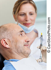Dentist Injecting Anesthesia - Female dentist injecting...