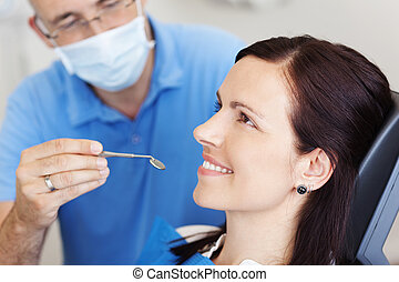 Examining Female Patients Mouth In Clinic - Mature dentist...