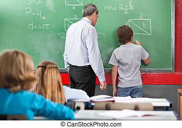 Schoolboy Solving Mathematics On Board In Classroom - Rear...